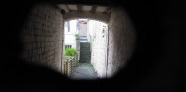A medieval courtyard seen through a small hole in an ordinary house front door.